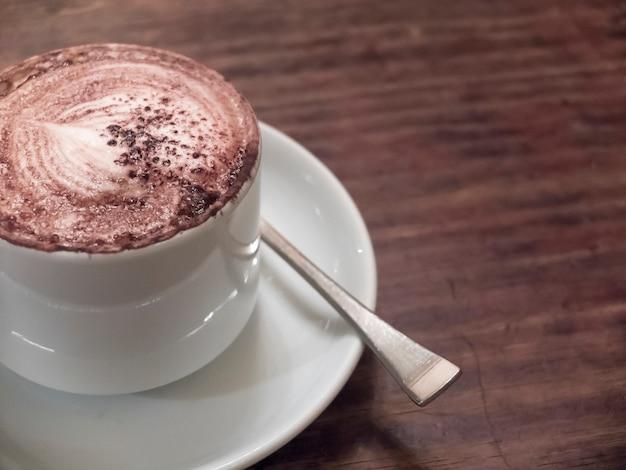 Schließen sie oben von einem köstlichen tasse kaffee auf holztisch.