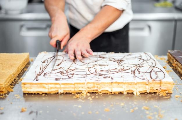 Schließen sie oben von einem konditor, der einen großen kuchen in portionen schneidet