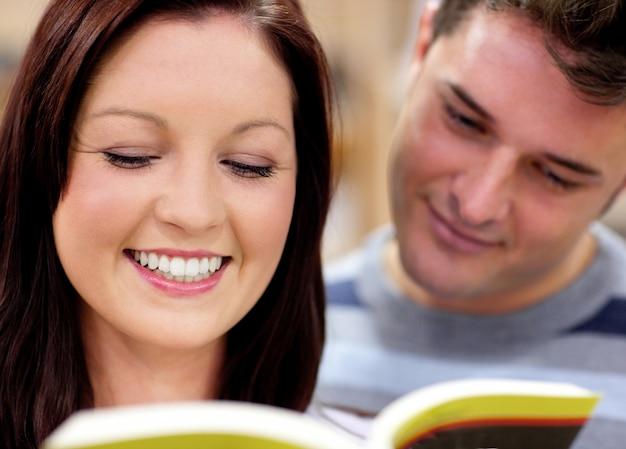 Schließen sie oben von einem lächelnden paar studenten, die ein buch lesen