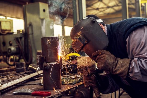Schließen sie oben von einem männlichen industriearbeiter in der schutzuniform, die metallrohr schneidet.