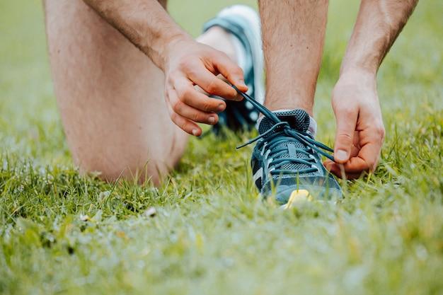 Schließen sie oben von einem mann, der die schnürsenkel auf diesen sportschuhen über grünem gras bindet, bevor sie fitness trainieren