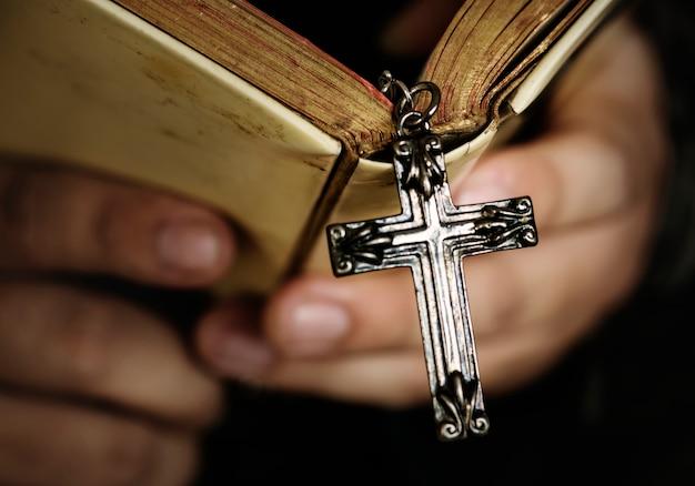 Schließen sie oben von einem mann, der eine bibel mit hängendem religions- und glaubenkonzept des kreuzes liest