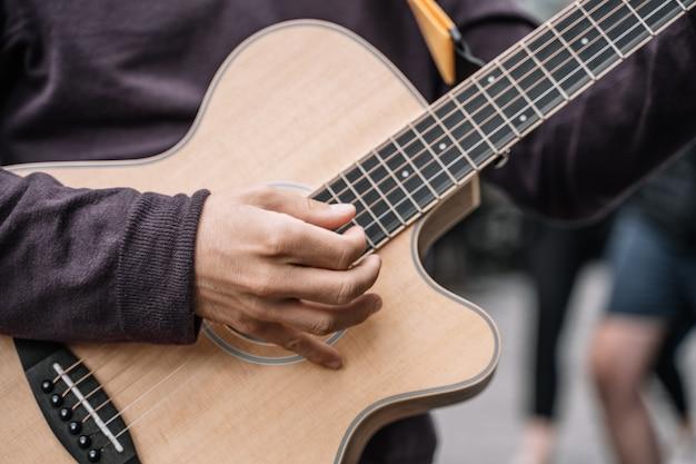 Schließen sie oben von einem mann, der eine gitarre, straßenausführender spielt.