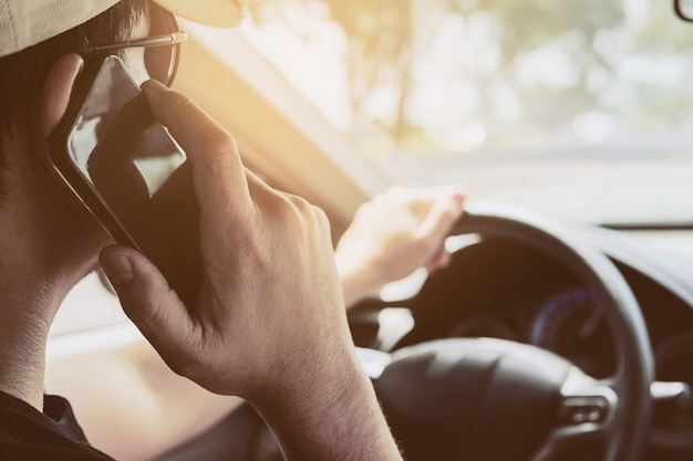Schließen sie oben von einem mann, der gefährlich auto während der verwendung des handys fährt