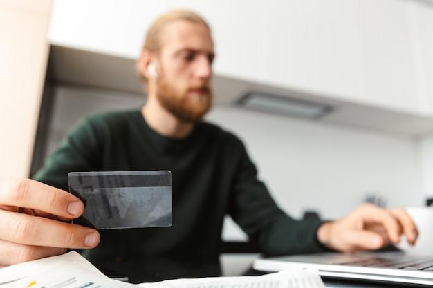 Schließen sie oben von einem mann, der kreditkarte zeigt, die zu hause am laptop arbeitet