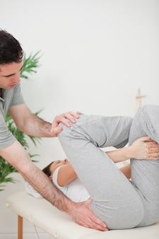 Schließen sie oben von einem physiotherapeuten, der einer frau für ihre übung hilft