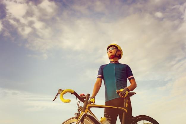 Schließen sie oben von einem radfahrermann, der mit einem rennrad bei sonnenuntergang, sportler im rennkonzept steht.