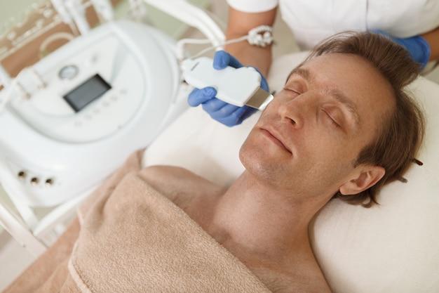 Schließen sie oben von einem reifen mann, der sich in der schönheitsklinik entspannt und gesichtsultraschallverfahren erhält