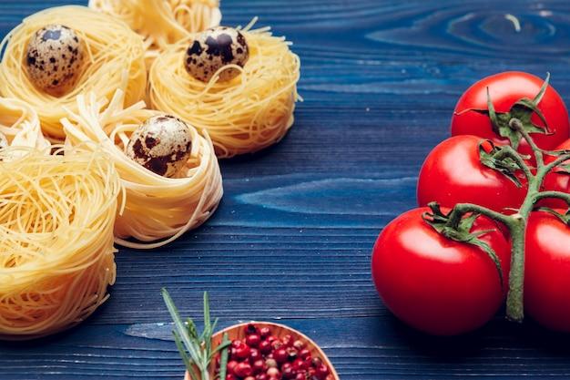 Schließen sie oben von einem rohen trockenen italienischen teigwarenfettuccine auf blauem hölzernem