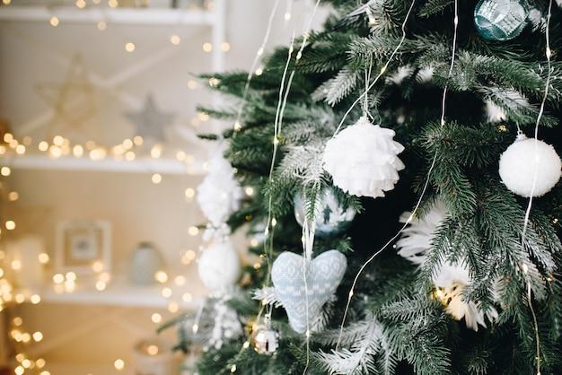Schließen sie oben von einem schön geschmückten weihnachtsbaum auf einem glitzernden