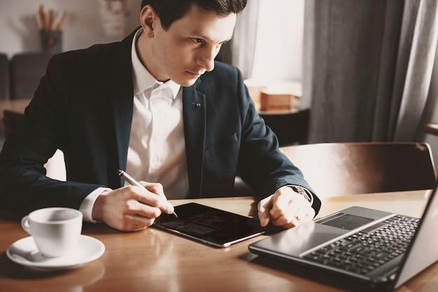 Schließen sie oben von einem selbstbewussten erwachsenen freiberufler, der eine website macht, während er in einem café sitzt.