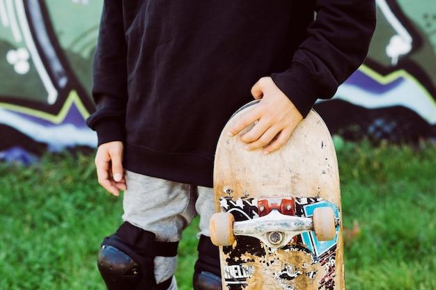 Schließen sie oben von einem skaterjungen mit einem alten skateboard vor einem graffiti-wandbild