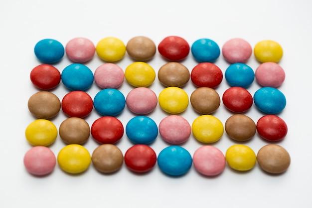 Schließen sie oben von einem stapel der bunten schokoladenüberzogenen süßigkeiten, schokoladenmuster, schokoladenhintergrund
