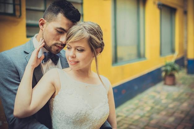 Schließen sie oben von einem stilvollen paar, das in stadtstraße der alten architektur umarmt. modische braut und bräutigam in der liebe