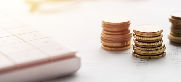 Schließen sie oben von einem taschenrechner und münzen auf einer finanzdatenwand
