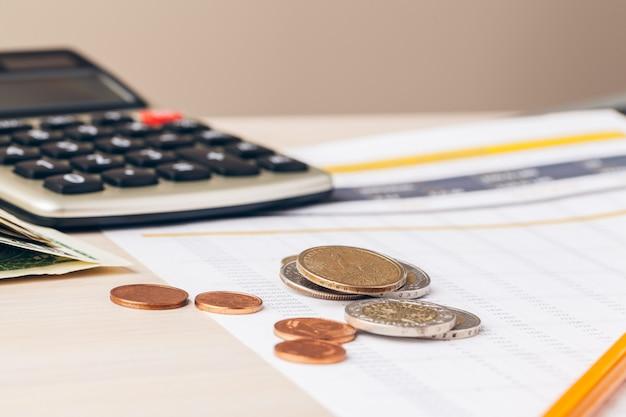 Schließen sie oben von einem taschenrechner und von den münzen auf einem geschäft