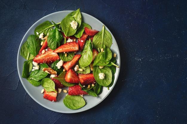Schließen sie oben von einem teller mit erdbeer-spinat-salat auf blauem hintergrund