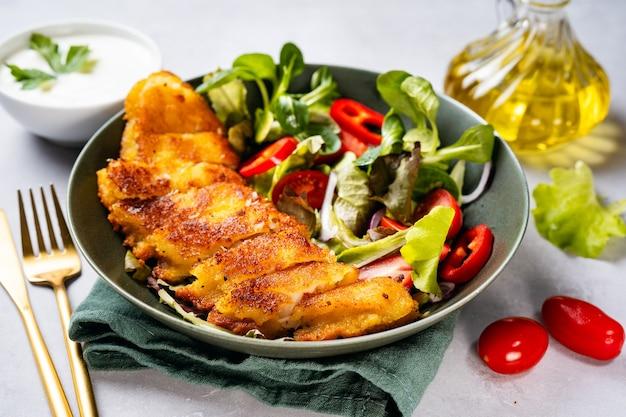 Schließen sie oben von einem teller mit köstlichem paniertem kabeljau mit gesundem salat
