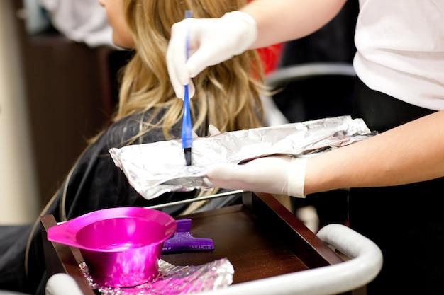 Schließen sie oben von einem weiblichen kunden, der ihr haar trocknet
