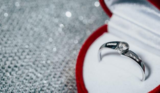 Schließen sie oben von einem weißgold-verlobungsring mit diamanten in der roten box, konzept der liebe