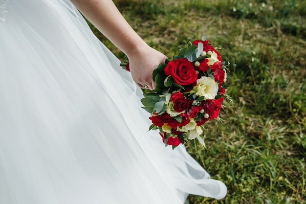 Schließen sie oben von einer braut, die einen hochzeitsblumenstrauß mit den roten und weißen rosen hält.