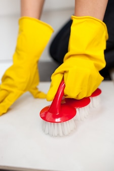 Schließen sie oben von einer frau, die einen badezimmerboden säubert