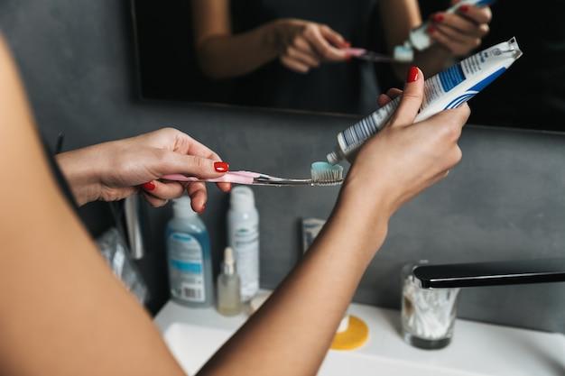 Schließen sie oben von einer frau, die zahnpasta auf eine zahnbürste in einem badezimmer setzt