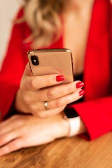 Schließen sie oben von einer frau im roten anzug unter verwendung des mobilen smartphones. blogger mit roter maniküre