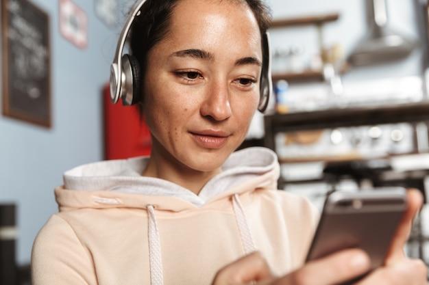 Schließen sie oben von einer glücklichen frau, die musik mit kopfhörern zu hause hört