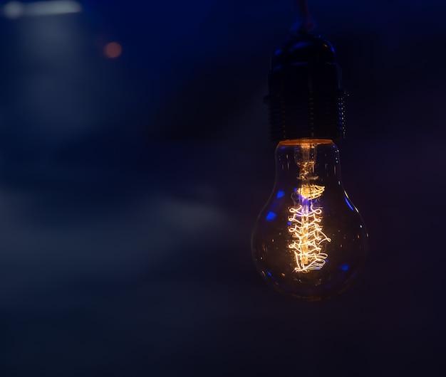 Schließen sie oben von einer glühenden glühbirne, die im dunklen kopierraum hängt.