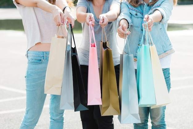 Schließen sie oben von einer gruppe jungen asiatin beim einkaufen in einem im freienmarkt mit einkaufstaschen