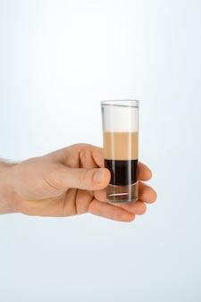 Schließen sie oben von einer hand, die ein glas b-52 cocktail auf weiß mit kopienraum hält.