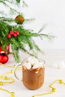 Schließen sie oben von einer heißen schokolade mit marshmallows neben dem weihnachtsbaum