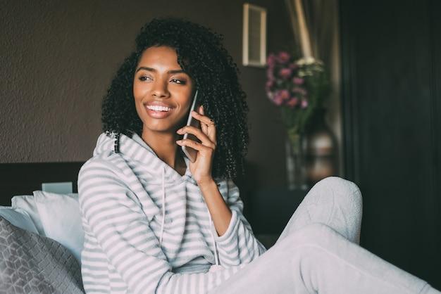 Schließen sie oben von einer hübschen schwarzen frau mit dem gelockten haar lächelnd und telefon auf dem bett verwendend, das weg schaut