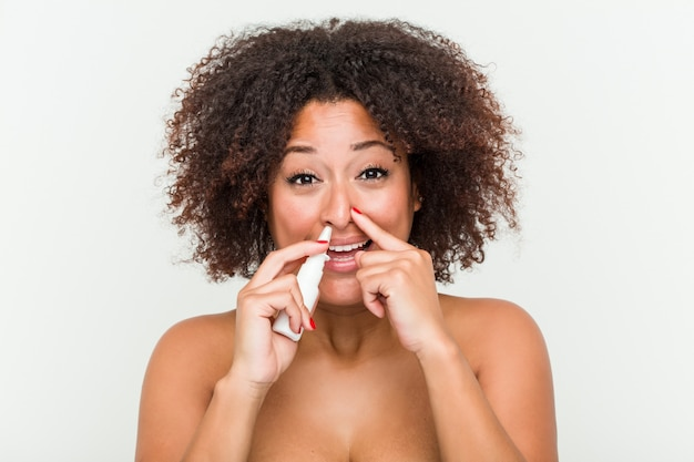 Schließen sie oben von einer jungen afroamerikanerfrau, die einen nasenspray verwendet
