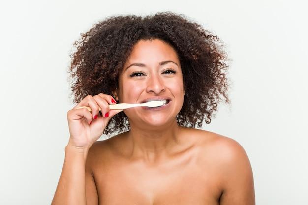 Schließen sie oben von einer jungen afroamerikanerfrau, die ihre zähne mit einer zahnbürste putzt