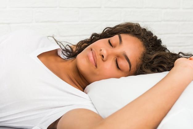 Schließen sie oben von einer jungen afroamerikanermüden frau, die auf dem bett schläft