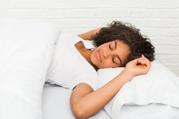 Schließen sie oben von einer jungen afroamerikanischen müden frau, die auf dem bett schläft