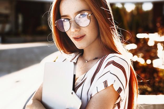 Schließen sie oben von einer jungen reizenden rothaarigen freiberuflerin mit sommersprossen, die kamera gegen sonnenuntergang betrachten, der einen laptop gegen ein gebäude hält.