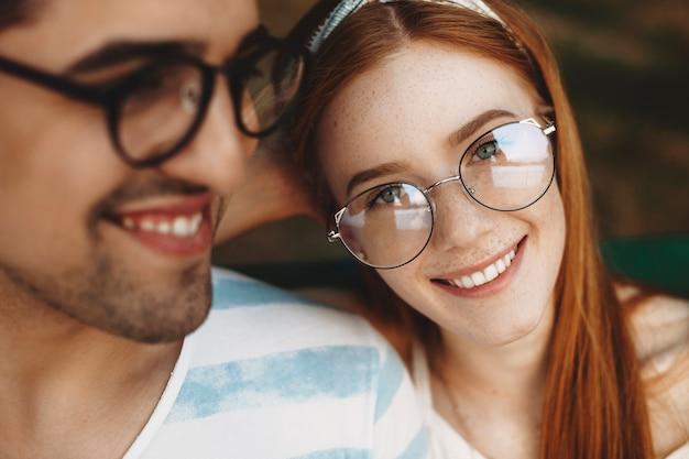 Schließen sie oben von einer jungen schönen frau mit roten haaren und sommersprossen lächelnd, die kamera betrachten. charmantes junges paar aus und spaß haben. zwei junge studenten aus