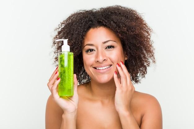 Schließen sie oben von einer jungen schönen und natürlichen afroamerikanerfrau, die eine aloe vera-flasche hält