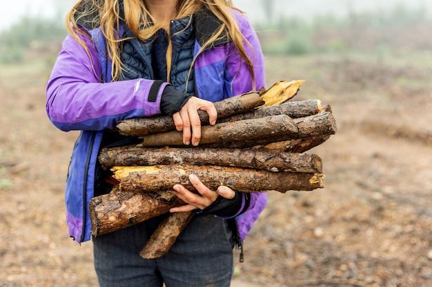 Schließen sie oben von einer kaukasischen frau, die brennholzprotokolle in einem nebligen wald hält, der lila regenmantel während eines regnerischen tages trägt