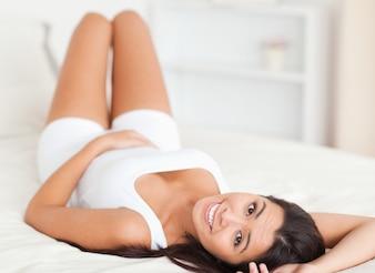 Schließen Sie oben von einer lächelnden Frau, die auf Bett liegt