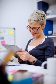 Schließen sie oben von einer reizenden lächelnden professionellen geschäftsfrau des kurzen haares, die im büro sitzt und in einer tablette schaut.
