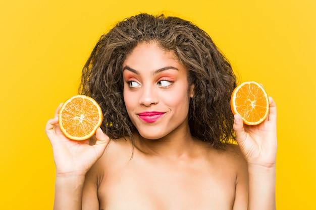Schließen sie oben von einer schönen jungen afroamerikaner- und make-upfrau, die eine pampelmuse hält
