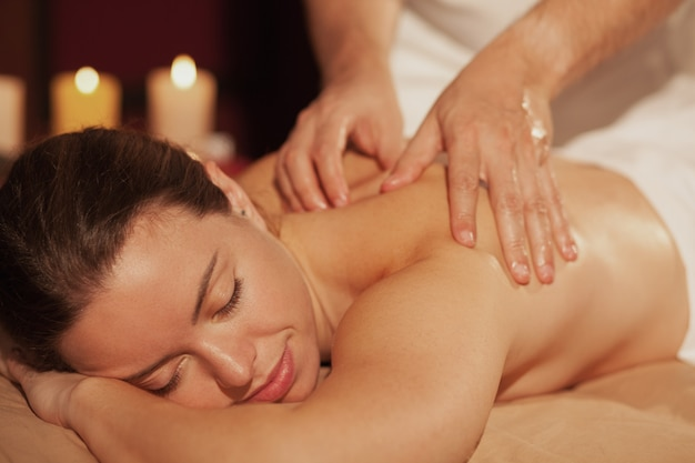 Schließen sie oben von einer schönheit, die massagetherapie in der badekurortmitte genießt. berufsmasseur, der zurück vom weiblichen kunden massiert. herrliche junge frau, die während der badekurortbehandlung sich entspannt. service, resort