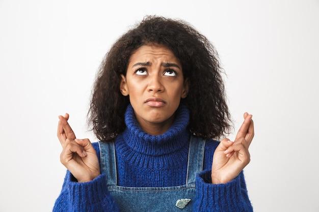 Schließen sie oben von einer ziemlich besorgten jungen afrikanischen frau, die pullover trägt, der isoliert steht und daumen drückt für glück