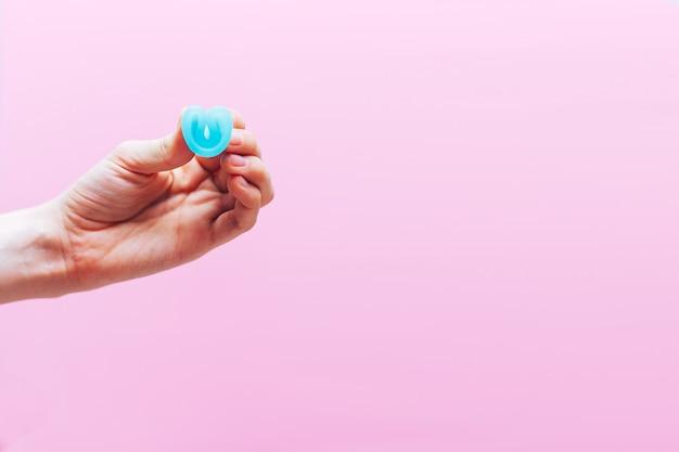 Schließen sie oben von faltender menstruationstasse der frauenhand, wie man, c-formular verwendet. frauengesundheitskonzept, null abfallalternativen
