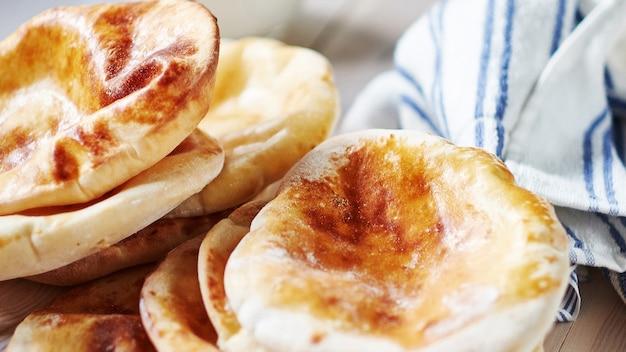 Schließen sie oben von fladenbrot pita mit milch am wodden weißen tisch. gebratener johnny-kuchen. östliche küche. asia flapjack. rustikaler stil.