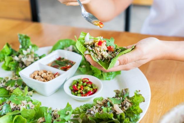 Schließen sie oben von frau, die gebratenen makrelen-würzigen salat isst, der mit frischem gemüse, chilis, erdnuss und thailändischer würziger fischsauce auf holztisch serviert wird